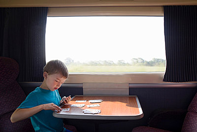 Young boy with playing cards on train - p429m824246f by Gary John Norman