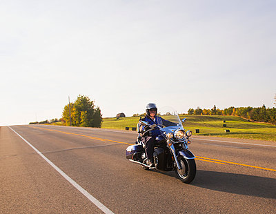 Mature man riding a motorcycle on highway; Edmonton, Alberta, Canada - p442m936280 by LJM Photo