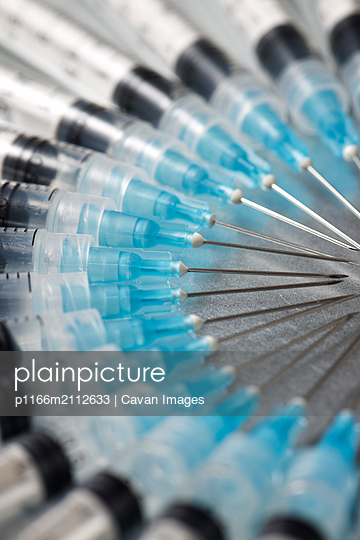 High angle close-up of syringes arranged on table - p1166m2112633 by Cavan Images