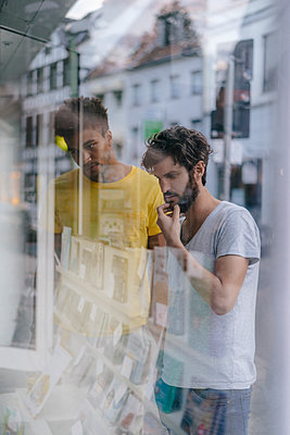 Two friends in the city looking in shop window of a bookstore - p300m1535209 by Kniel Synnatzschke