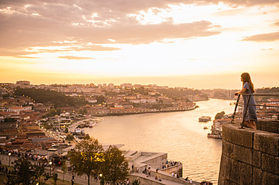 Woman watching panoramic view of Porto at sunset, Portugal - p300m2139561 by Hernandez and Sorokina