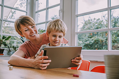Mother holding digital tablet with son while sitting at home - p300m2226254 by Mareen Fischinger