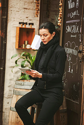 Spain, Catalunya, Barcelona, young black dressed businesswoman looking at her smartphone in front of a wine bar - p300m980999f by Bonninstudio