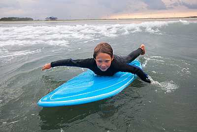 A Boy Surfs At Nahant Beach In Nahant, Massachusetts - p343m1416079 by Laurie Swope