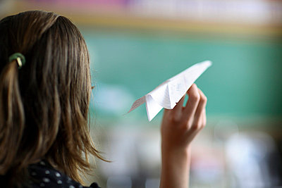 Teen girl holding paper airplane - p3721899 by James Godman
