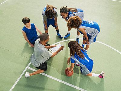 Basketball team talking on court - p555m1415520 by Erik Isakson