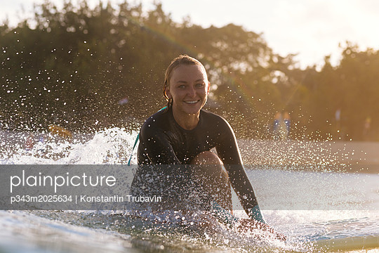Young woman smiling at camera while surfing near coast, Kuta, Bali, Indonesia - p343m2025634 by Konstantin Trubavin