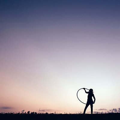 Silhouette girl playing with hula hoop against clear sky - p1166m1182590 by Cavan Images