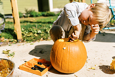 Child carving out pumpkins for halloween on their patio - p1166m2218607 by Cavan Images