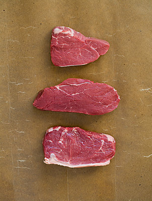 Three pieces of meat against brown background - p1629m2211309 by martinameier