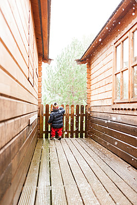 Back view of little boy standing between two log cabins in winter - p300m1120551f by Valentina Barreto