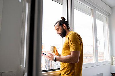 Handsome man using smart phone while standing near window at home - p300m2281967 by Jose Carlos Ichiro