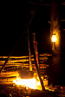 Food being cooked in container on campfire in forest at night - p426m1468491 by Fredrik Telleus
