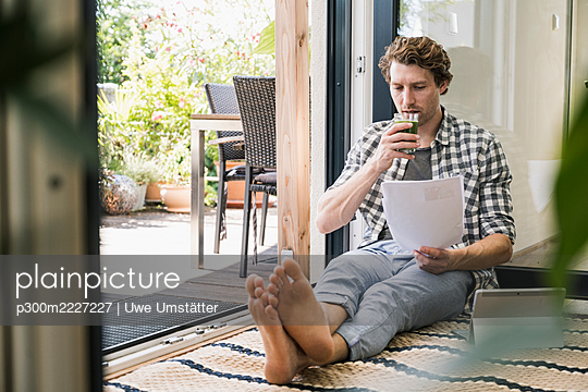 Mid adult man drinking juice holding paper while sitting at home - p300m2227227 by Uwe Umstätter