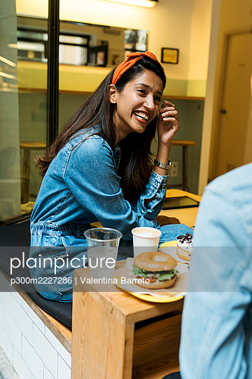 Smiling woman talking with friend while having food sitting at cafe - p300m2227286 by Valentina Barreto