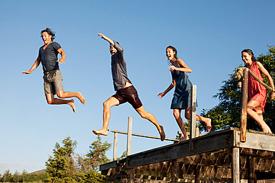 Enthusiastic friends jumping off dock - p1023m756144f by Sam Edwards