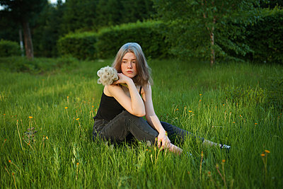Young woman sits in a meadow holding dandelion clocks - p1646m2264269 by Slava Chistyakov