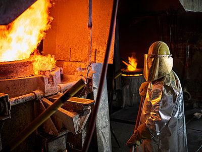 Industry, worker at furnace during melting copper, wearing a fire proximity suit - p300m2102610 von Christian Vorhofer