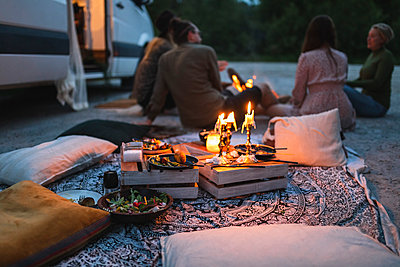 Female and male friends talking by camping van during vacation - p426m2296292 by Maskot
