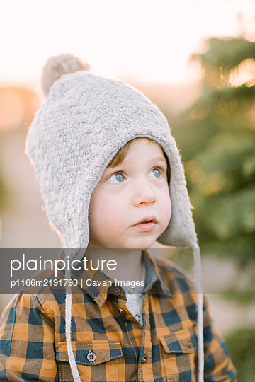 Toddler wearing winter hat looks up magical, holiday, thoughtful - p1166m2191793 by Cavan Images