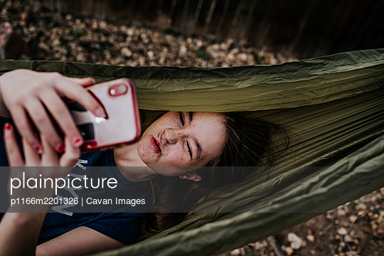 Teen girl laying in hammock making silly faces into phone - p1166m2201326 by Cavan Images