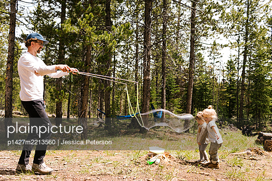 Father making large soap bubbles in forest for two daughters (2-3, 4-5), Wasatch-Cache National Forest - p1427m2213560 by Jessica Peterson