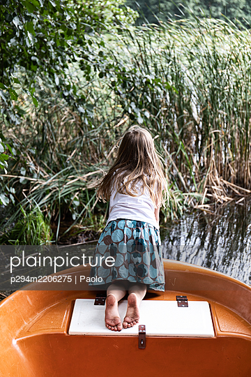 Girl in rowing boat watching reed - p294m2206275 by Paolo