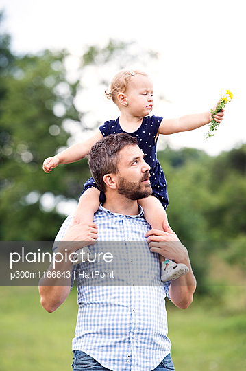 Father carrying little daughter on shoulders in nature - p300m1166843 by HalfPoint
