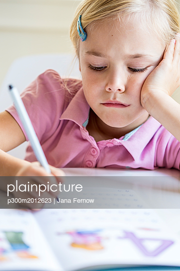 Portrait of bored little girl writing numbers in exercise book - p300m2012623 von Jana Fernow