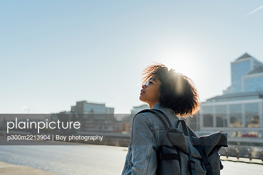 Young woman with backpack standing against clear sky in city during sunny day - p300m2213904 by Boy photography