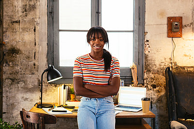 Portrait of smiling young woman standing front of desk in a loft - p300m1580773 by Bonninstudio