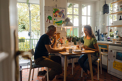 Mature couple sitting at kitchen table at home - p300m2029656 by Kniel Synnatzschke