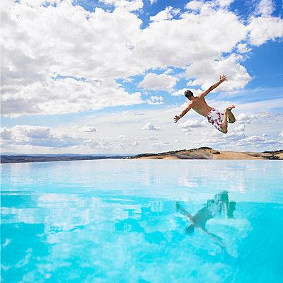 Man jumping in swimming pool - p4295624 by Aurelie and Morgan David de Lossy