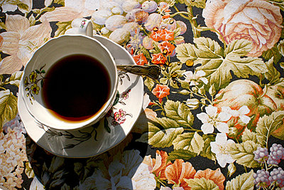 Teacup and saucer on floral tablecloth - p9241969 by Alexander Porter