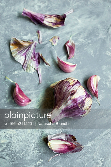 Close-up of purple garlic on table - p1166m2112231 by Natascha Brandt
