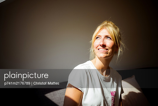 Young woman in her attic in the sunlight - p741m2176789 by Christof Mattes