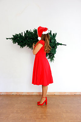 Woman with christmas cap carrying christmas tree - p1105m2215079 by Virginie Plauchut