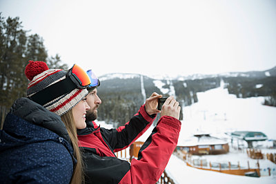 Skier couple with camera phone photographing snowy view from ski resort balcony - p1192m1546591 by Hero Images