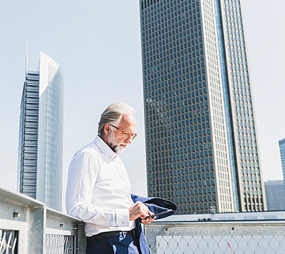 Mature businessman in the city using cell phone - p300m1587336 by Uwe Umstätter