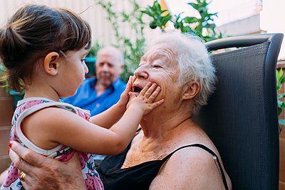 Grandmother and granddaughter playing together on terrace - p300m2029075 by Gemma Ferrando