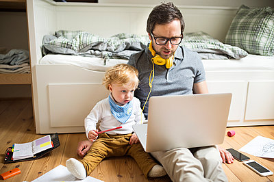 Father at home with his little son and laptop - p300m2069940 by HalfPoint
