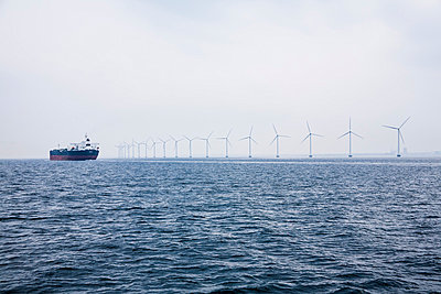 Germany, Hamburg, View of cargo ship in front of the wind-wheels of an offshore windpark - p300m878112 by Dieter Schewig