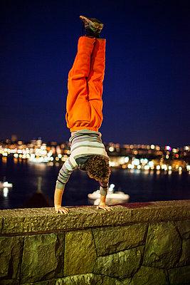 Man doing handstand at night - p312m998662 by Kari Kohvakka