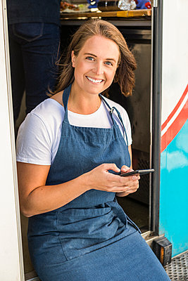 Portrait of smiling young female owner using smart phone while sitting at food truck entrance - p426m2046494 by Maskot