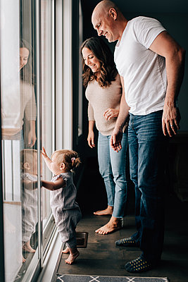 Mother and father with baby daughter looking out through patio door - p924m2097597 by Sara Monika