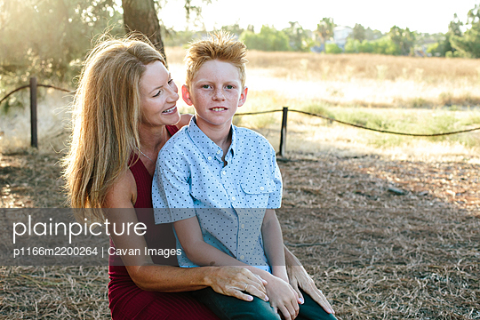 A Cute Boy With Red Hair Sits On His Mother's Lap While Outside - p1166m2200264 by Cavan Images