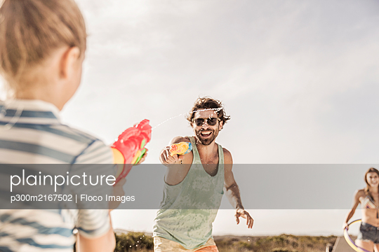 Father and daughter having a water fight - p300m2167502 by Floco Images