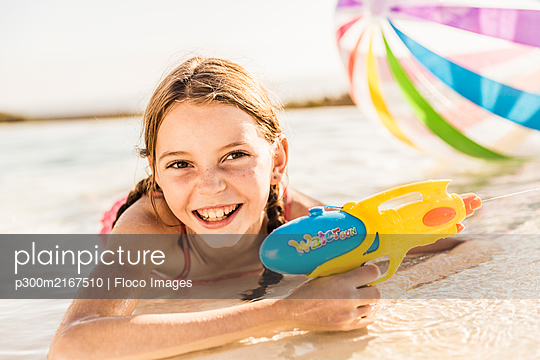 Portrait of cute girl lying in swimming pool with water gun - p300m2167510 by Floco Images