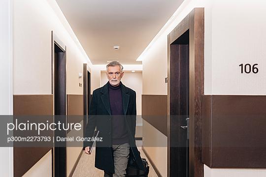 Mature businessman walking with laptop at corridor in hotel - p300m2273793 by Daniel González