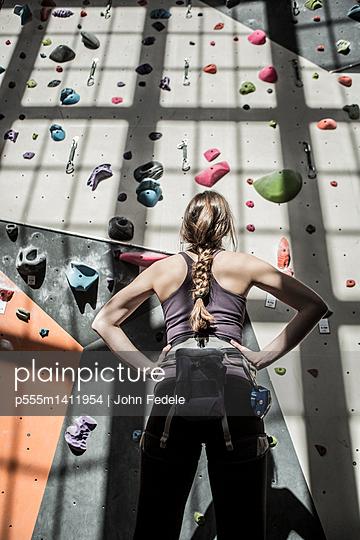 Athlete examining rock wall in gym - p555m1411954 by John Fedele